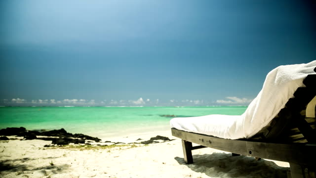 sunchair at beach in mauritius with parasailer video