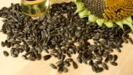 Sunflower seeds, sunflower flower on the wooden table, sunflower oil is poured in a glass bowl, tilt video