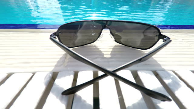 Sunglasses at poolside of hotel swimming pool outdoor video