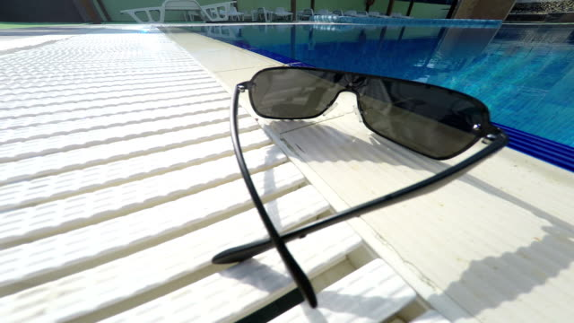 Sunglasses at the edge of hotel swimming pool outdoor video
