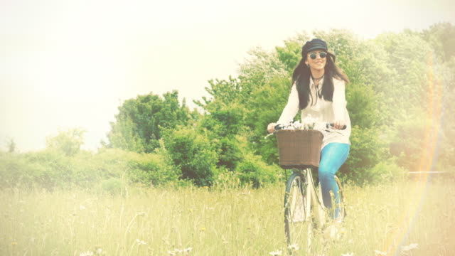Sunlight and cycling. Young woman riding a retro bike though a meadow. Slow motion. video