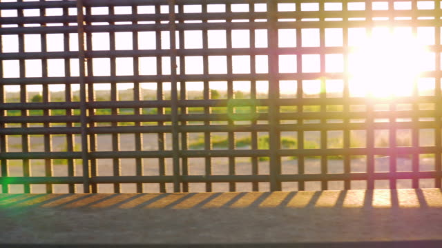 Sunlight Flickers Between the Bars of the Border Fence Dividing Countries video