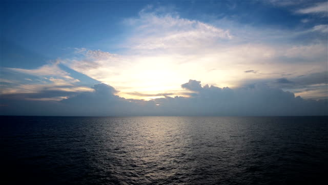 Sunlight Reflecting off Pretty Ocean ripple with Beautiful Clouds in blue Sky - Around Sunset?Sun Setting Soon over Horizon on Sea video