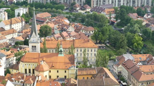 Sunlit ancient Saint James Parish Church in Slovenia, sunny green Ljubljana, pan video