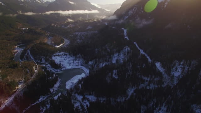 Sunny Helicopter View of Mountain Valley with River in Snow Dusted Forest video