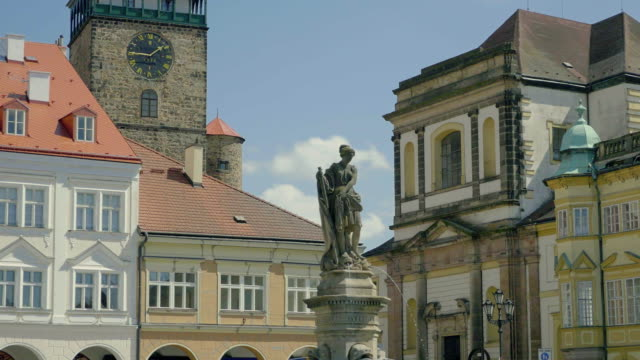 Sunny medieval Renaissance square with stone sculpture, tower and clock. video