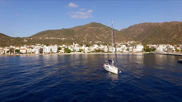 Sunny Morning in an empty Greek marina, Methana, Mediterranean Sea. Aerial video shooting, the height of a bird's flight. A lone sailing yacht leaves the marina. In the background is a landscape of mountains and city buildings. Summer clear morning, blue video