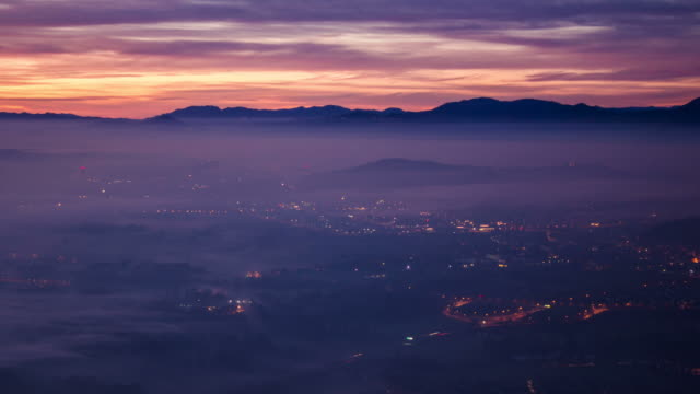 Sunrise of a mountain panorama over the city with a dense foggy layer video