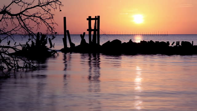 Sunrise of water with rocks and pier pieces video
