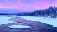 Sunrise over river rapids in a winter landscape, Finnish Lapland video