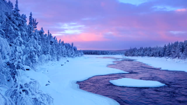 Sunrise over river rapids in a winter landscape, Finnish Lapland video