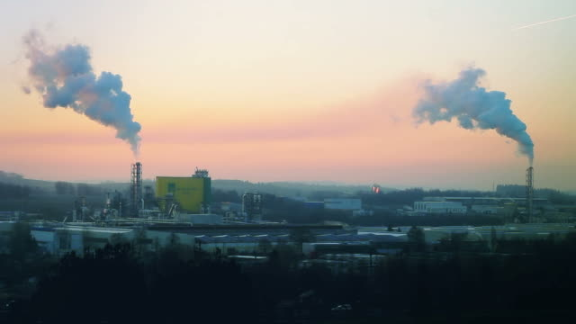 Sunrise silhouette of smoking factory video