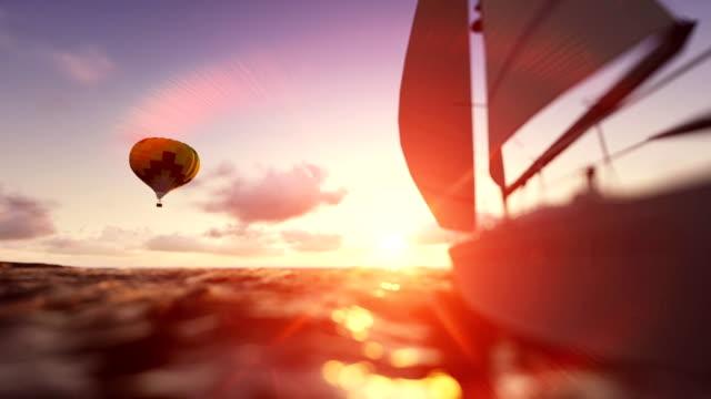 Sunrise summer time, air balloon and yacht sailing video