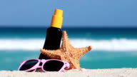 Sunscreen protection cream, starfish and sunglasses on white sand against turquoise caribbean sea water video