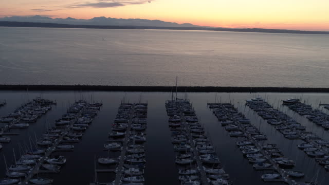 Sunset Aerial of Ocean with Mountain Range Background and Luxury Boats Docked video