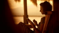 Sunset and beach on the island of Bali. The girl in a striped blouse and wide trousers in the evening sitting on a soft chair by the beach. It plays on your tablet video