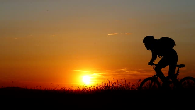 Sunset and rear view of mountain cyclist riding-slow motion video