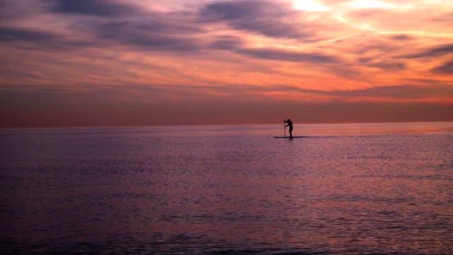 Sunset at sea. Man on surfboard at sunset. Sea sunset. Sunset landscape video