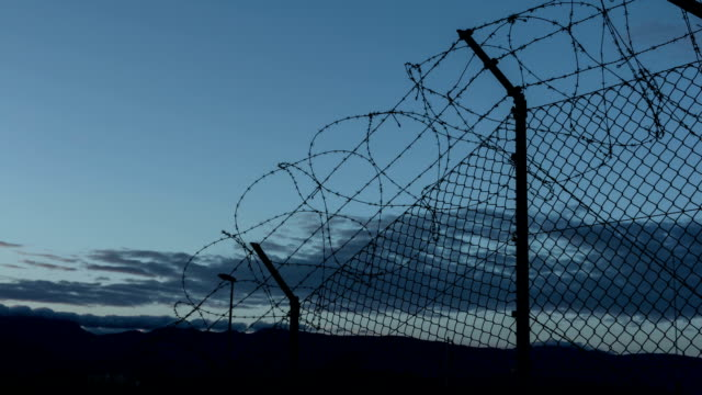 Sunset behind a barbed wire in prison. Time-lapse video