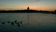 Sunset kayaking on lake in front of government building video