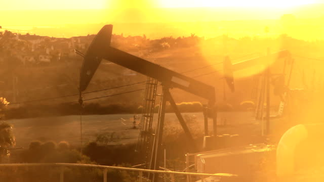 Sunset Oil Derricks on Sunny Coastline video