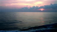 sunset on waving sea, with a cruiser on the horizon, view from bottom deck of moving cruiser video