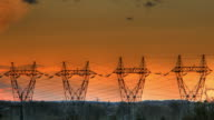 Sunset over electricity pylons time lapse video