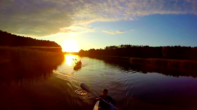 Sunset over river, silhouettes of people in boats, traveling video