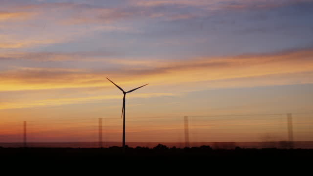 Sunset over the countryside with a wind generator. View from the window of a traveling car video