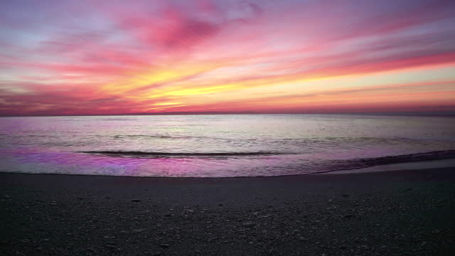 sunset scene with sea calm and sun fall behind the clouds in background, warm colorful sky video