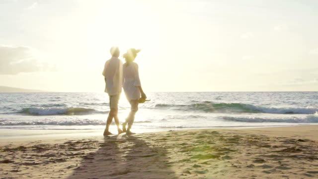 Sunset Walk on a Luxury Beach. Happy Retired Couple on Tropical Vacation. Slow Motion video