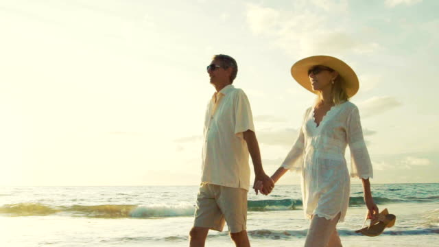 Sunset Walk on a Tropical Beach. Happy Retired Couple on Tropical Vacation. video