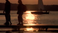 Sunset with sailboat and people walking video