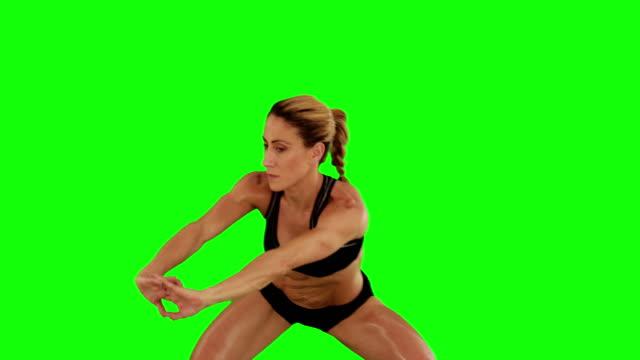 Super fit woman doing sumo squats video