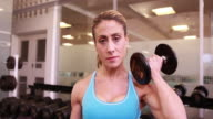 Super fit woman lifting dumbbells at gym video