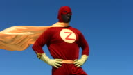 Super hero with cape flying in wind, slow motion video