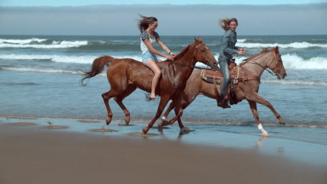 Super slo mo women riding horses at beach video