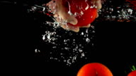 Super slow motion close up shot of hand reaching and grabbing tomato under water video