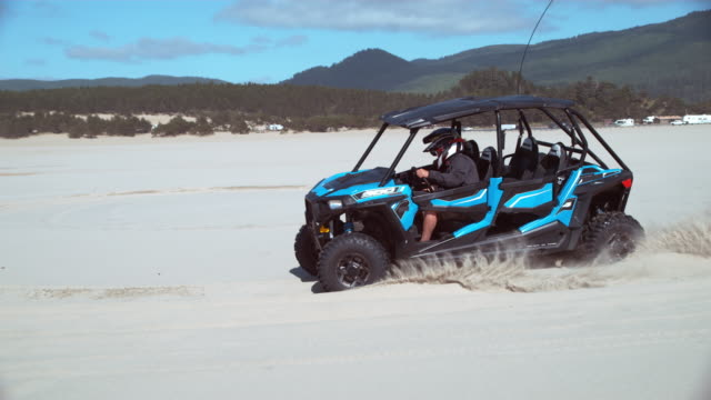 Super slow motion shot of ATV driving on sand dunes video