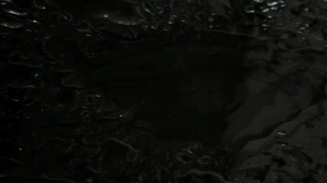 Super slow motion shot of  water drops hitting wet glass surface video