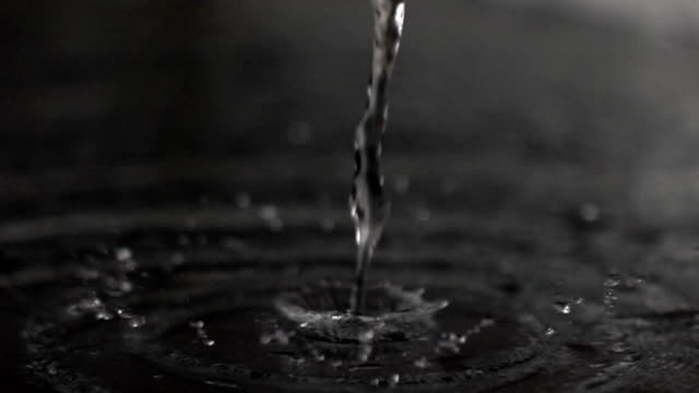 Super slow motion video of water flow hitting dark smooth surface video