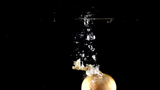 Super slow motion: whole onion falling into water, black background video