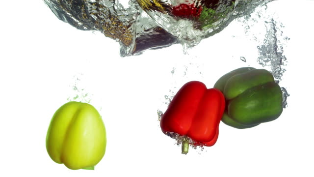 HD Super Slow-Mo: Bell Peppers Falling Into Water video