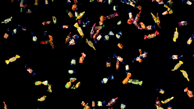 HD Super Slow-Mo: Candies Falling Over Black Background video