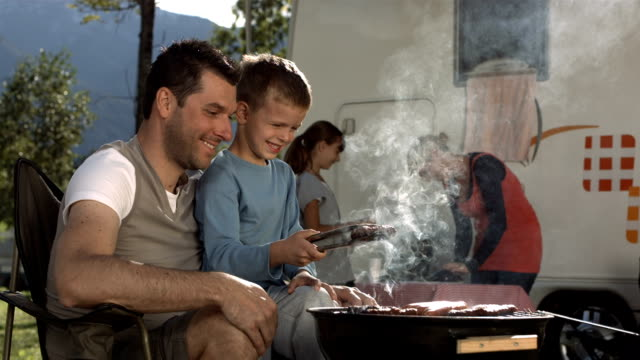 HD Super Slow-Mo: Father And Son Grilling Meat On Barbecue video