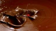 HD Super Slow-Mo: Few Strawberries Splashing Into Chocolate video