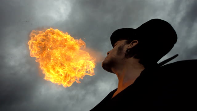 HD Super Slow-Mo: Fire Breather Against Cloudy Sky video
