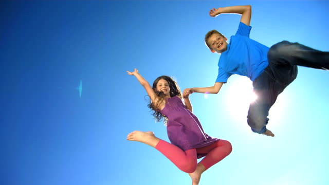 HD Super Slow-Mo: Happy Siblings Jumping In The Air video