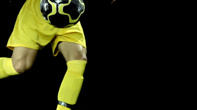 HD Super Slow-Mo: Kicking A Ball On Black Background video