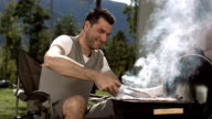 HD Super Slow-Mo: Man Grilling Meat On Barbecue video